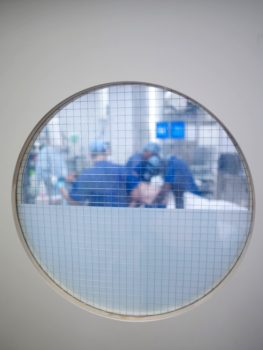Photograph of a surgery taken through an operating theatre window